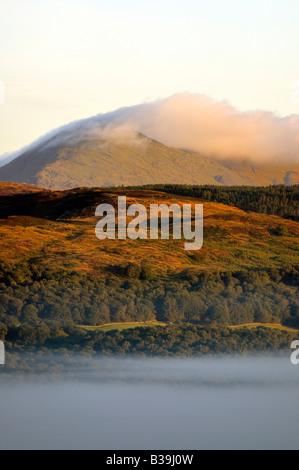 Early morning fog in the Rusland valley with cloud lifting off the Coniston fells and Dow crag - Stock Photo