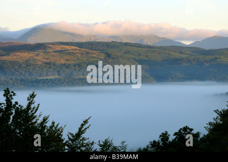 Early morning fog in the Rusland valley with cloud lifting off the Coniston fells, Coniston Old Man and Dow crag - Stock Photo