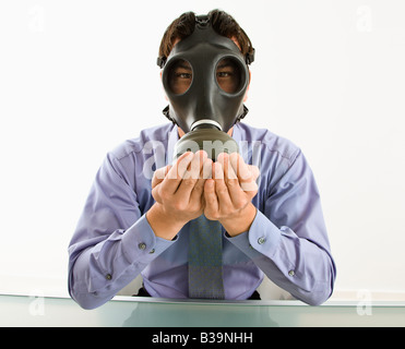 Businessman sitting wearing gas mask holding his hands over his mouth - Stock Photo