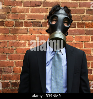 Businessman standing next to brick wall wearing gas mask - Stock Photo