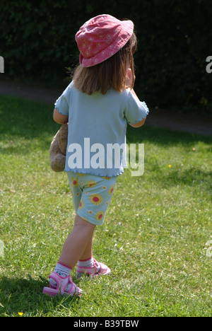 Rear view of a little girl holding a teddy bear and wearing shorts and a sunhat walking away - Stock Photo