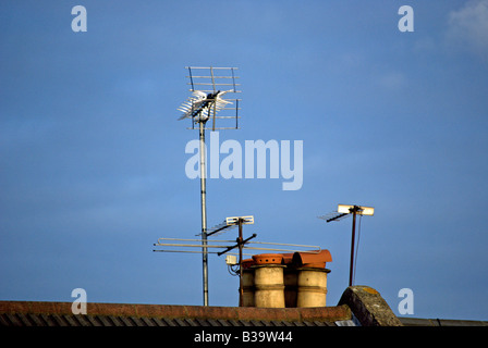 seen against a blue sky, tv aerials and victorian chimney pots on a residential rooftop in twickenham, middlesex, - Stock Photo