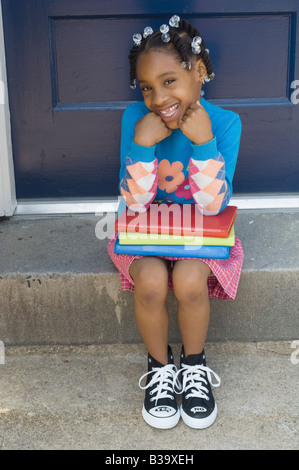 African girl sitting with school books