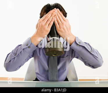 Businessman sitting wearing gas mask holding his hands over his eyes - Stock Photo