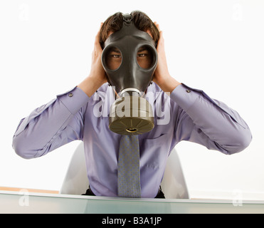 Businessman sitting wearing gas mask holding his hands over his ears - Stock Photo