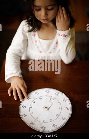 Five year old girl tells the time with a paper clock her older brother made at school - Stock Photo