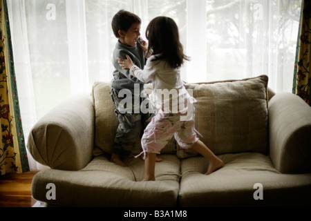 Brother aged six and sister five wrestle on sofa beside window - Stock Photo