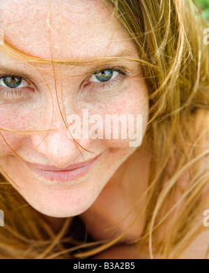 Close up portrait of attractive redheaded woman looking at viewer - Stock Photo