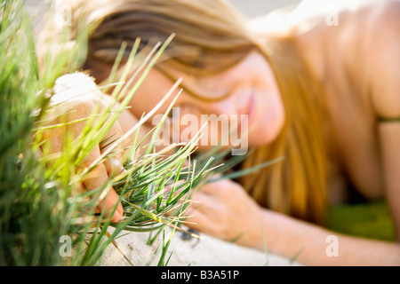 Selective focus portrait of young redheaded woman lying in grass looking at viewer - Stock Photo