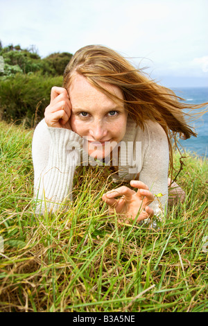 Portrait of young redheaded woman lying in grass looking at viewer with devilish grin - Stock Photo