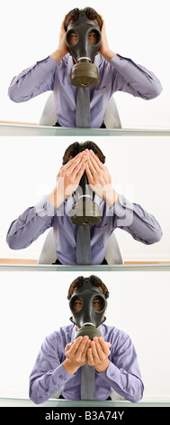 Businessman sitting wearing gas mask holding his hands over his ears eyes mouth - Stock Photo