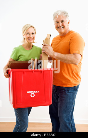 Man and woman smiling while holding recycling bin - Stock Photo