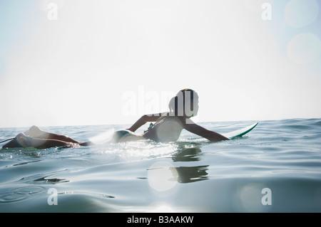 Hispanic girl paddling on surfboard - Stock Photo