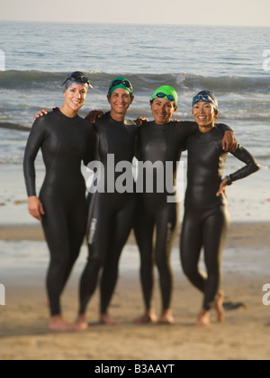 Multi-ethnic women wearing wetsuits and goggles - Stock Photo