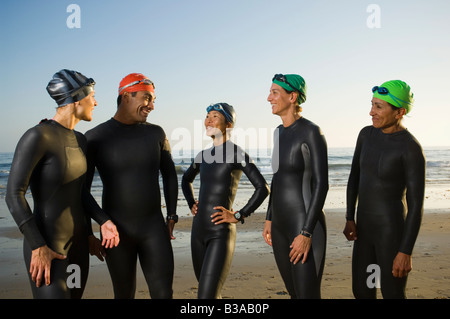 Multi-ethnic swimmers wearing wetsuits and goggles - Stock Photo