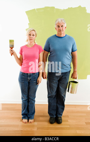 Portrait of unhappy adult couple standing in front of half painted wall with paint supplies American Gothic style - Stock Photo