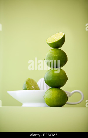 stack of green limes and juicer on a green background - Stock Photo