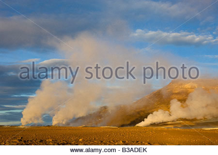Several fumeroles shoot steam high into the sky at sunrise at Hverir, an especially active geothermal field in northern - Stock Photo