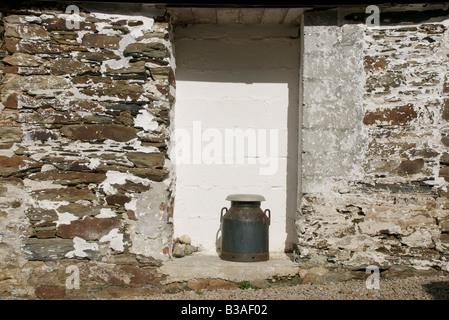 Metal churn outside old doorway of rural barn - Stock Photo