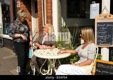 UK Cheshire Tarporley High Street three women chatting on pavement outside cafe - Stock Photo