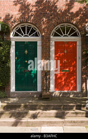 UK Cheshire Tarporley Red and Green painted front doors of newly built Georgian style terraced houses - Stock Photo
