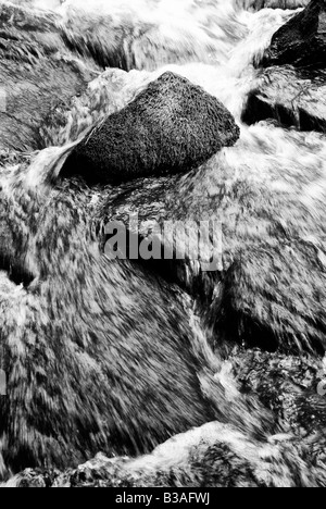 Close up of blurred water rushing between rocks at ButterMilk Falls - Stock Photo