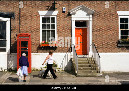 UK Cheshire Tarporley High Street K6 phone box outside former post office near red painted front door - Stock Photo