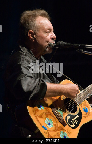 Argentinian folk musician Leon Gieco playing harmonica and guitar in a concert in Cordoba Argentina - Stock Photo