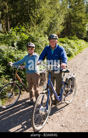 UK Cheshire Delamere Forest Park man and woman cyclists with Giant electrically assisted bikes - Stock Photo
