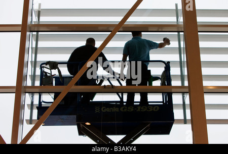 Two window cleaners cleaning a large window of an outlet store, gloucester, england, uk - Stock Photo