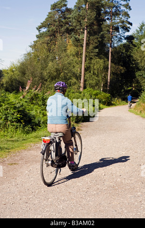 UK Cheshire Delamere Forest Park older woman cyclist on Giant electrically assisted bike - Stock Photo