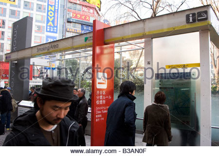 People walk past, and stand close to, an information stand and smoking area in central Tokyo. Japan. The stand is - Stock Photo