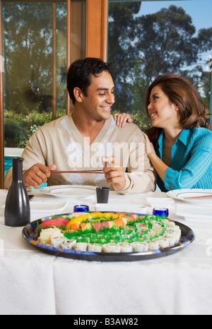 Multi-ethnic couple eating sushi - Stock Photo