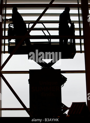 A silhouette of two window cleaners cleaning a large window of an outlet store, gloucester, england, uk - Stock Photo