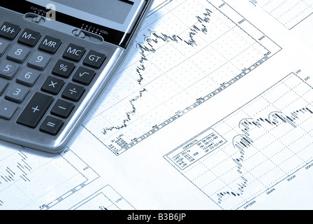 Calculator laying on printed stock market graphs, charts, graph, chart with bullish trend. - Stock Photo