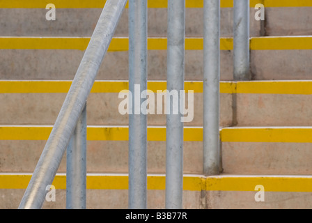 Metal railings and concrete steps with yellow painted edges at a stadium in the uk - Stock Photo