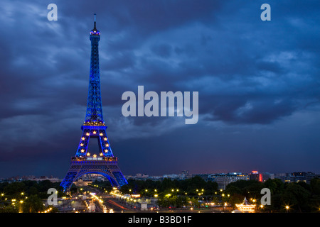 Wide-angle night view Eiffel Tower lit with special star & blue lights, Paris cityscape, summer twilight with approaching - Stock Photo
