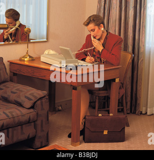 Business woman conversing on 'phone in hotel room. - Stock Photo