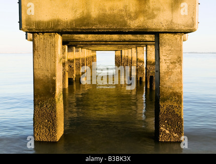 Underneath the concrete base of the pier at Lighthouse Beach on Sanibel Island Florida looking out at the Gulf of - Stock Photo