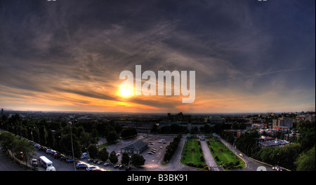 A stunning sunset on the horizon, with a parking lot in the foreground, and the industrial scenery, block apartments - Stock Photo