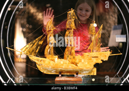 Young visitor looking at the amber model of a sailing ship in Deutsches Technikmuseum Berlin, Germany - Stock Photo