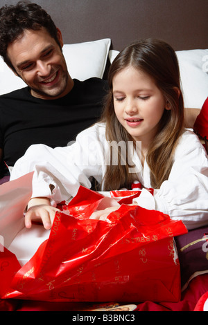 Father and Daughter Opening Christmas Presents - Stock Photo