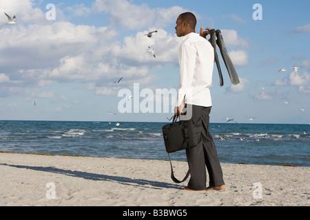 African businessman standing on beach - Stock Photo