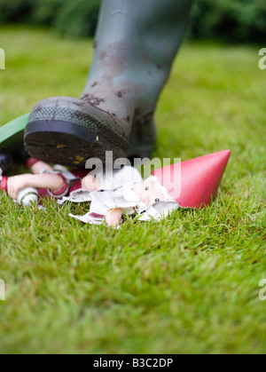 A foot trampling on a garden gnome - Stock Photo