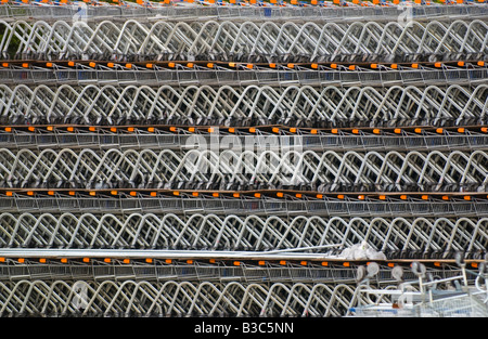 Stacked shopping trolleys waiting dispatch to supermarkets UK - Stock Photo