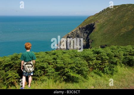 UK, Wales, Pembrokeshire. A young boy looks out from Dinas Head on a walk along the Pembrokeshire Coastal Path (MR). - Stock Photo