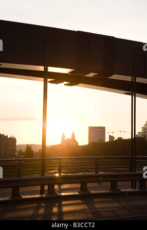 Sunset seen through girders of  the new King Mindaugas Bridge on the Neris River, in Vilnius, Lithuania. - Stock Photo
