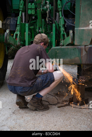 A young man using Grinding equipment on agricultural machinery - Stock Photo