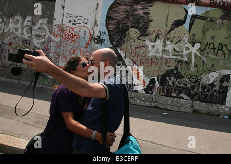 Couple kissing in front of Brezhnev and Honecker's kiss pictured on the Berlin Wall in East Side Gallery in Berlin, - Stock Photo