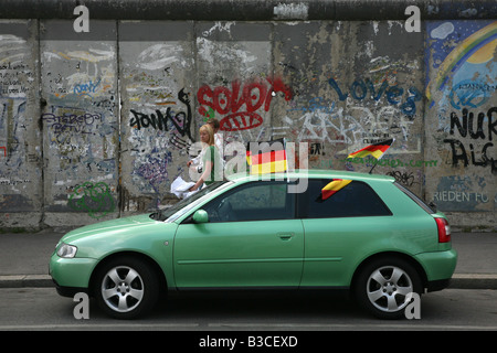 Car decorated by German national flags parked near the Berlin Wall in East Side Gallery in Berlin Germany